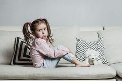Sad or angry little girl, victim, holding toy dog. royalty free stock image