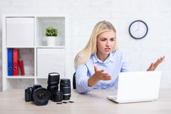 Sad or angry photographer with camera and photography equipment having problems with computer. Sad or angry female photographer with camera and photography royalty free stock image
