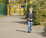 A sad or angry six year old boy. Walking through the park stock photos
