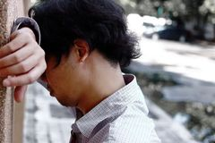 Sad anxious young Asian business man suffering from severe depression. Sad anxious young Asian business man suffering from severe depression Royalty Free Stock Photo