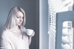 Sad apathetic lonely woman with a cup of coffee looking through a window at home or hotel, divorce, depression and apathy concept.  stock photos