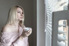 Sad apathetic lonely woman with a cup of coffee looking through a window at home or hotel, divorce, depression and apathy concept.  royalty free stock photos