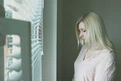 Sad apathetic lonely woman looking through a window at home or hotel, divorce, depression and apathy concept.  royalty free stock photography