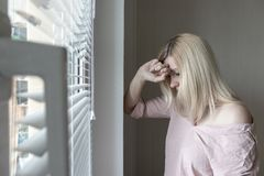 Sad apathetic lonely woman looking through a window at home or hotel, divorce, depression and apathy concept stock photos