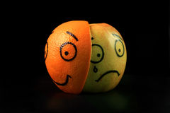Sad apple with happy orange mask Royalty Free Stock Photos