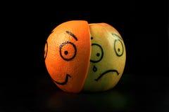 Sad apple with happy orange mask Royalty Free Stock Photos