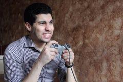 Sad arab egyptian businessman playing playstation Stock Photo
