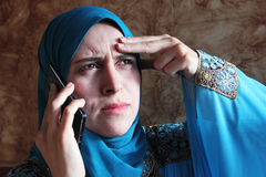 Sad arab muslim businesswoman with mobile Stock Images
