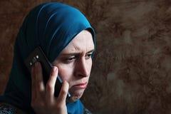Sad arab muslim businesswoman with mobile Royalty Free Stock Photos