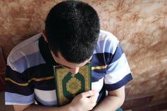 Sad arab muslim man with koran or quran holy book Royalty Free Stock Photos