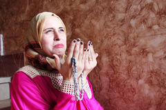 Sad arab muslim woman asking allah with rosary. Sad crying arabian egyptian muslim woman asking allah and searching hope with rosary in hand Royalty Free Stock Image