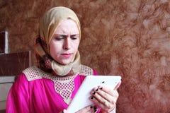 Sad arab muslim woman with tablet. Arabian egyptian muslim businesswoman feeling sad looking at her tablet Stock Photos