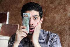 Sad arab young businessman with dollar bill money. Arab young muslim business man feeling sad and shocked with dollar bills on one of his eye Royalty Free Stock Image