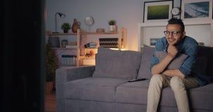 Sad Arabian guy watching TV crying wiping eyes sitting on couch alone at night. Sad Arabian guy is watching tv crying wiping eyes sitting on couch alone at night stock video footage