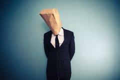 Sad and ashamed businessman with bag over head Stock Images