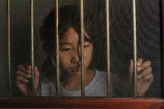 Sad asian child standing behind the wire screen window in dark m Stock Photo