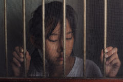 Sad asian child standing behind the wire screen window in dark m royalty free stock photography