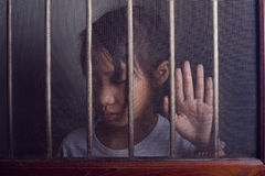 Sad asian child standing behind the wire screen window in dark m Stock Photography