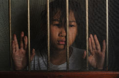 Sad asian child standing behind the wire screen window in dark m stock image