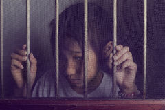 Sad asian child standing behind the wire screen window in split Royalty Free Stock Images