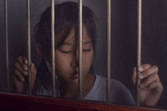 Sad asian child standing behind the wire screen window in split stock photo