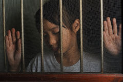 Sad asian child standing behind the wire screen window.  Unhappy. Kid  alone at home. Upset in the dark room Stock Images