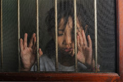 Sad asian child standing behind the wire screen window.  Unhappy. Kid  alone at home. Upset in the dark room Royalty Free Stock Photo