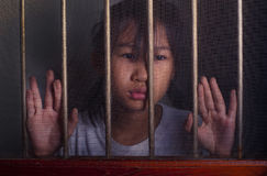 Sad asian child standing behind the wire screen window. Unhappy royalty free stock photo