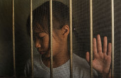 Sad asian child standing behind the wire screen window.  Unhappy. Kid  alone at home. Upset in the dark room Stock Photos