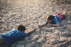 Sad Asian children tired and exhausted on cracked dry ground. Concept drought and shortage of water crisis Stock Photos