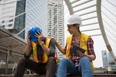 Sad Asian engineer in city. Sad engineer raise hands to relief headache while American female manager try to cheer him up. Depress or stressed working men after Stock Photo