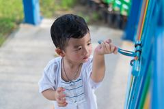 Sad Asian kid behind the grid trying to escape. shallow DOF Stock Photo
