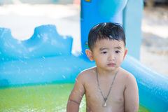 Sad Asian kid playing alone in inflatable baby pool. Royalty Free Stock Photos