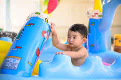Sad Asian kid playing alone in inflatable baby pool. Stock Image