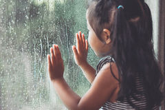 Free Sad Asian Little Girl Looking Outside Through The Window Royalty Free Stock Photos - 94283048