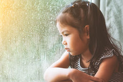 Sad asian little girl looking outside through the window. In the rainy day in vintage color tone Royalty Free Stock Images