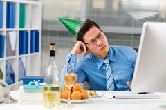 Sad Asian manager. In a party hat looking at the computer screen Stock Photo