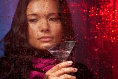 Sad Asian woman with drink in cold rainy weather Stock Images