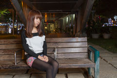 Sad Asian Woman on a Park Bench Stock Images