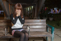 Sad Asian Woman on a Park Bench Stock Photo