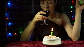 An attractive woman celebrates a holiday alone. Sad attractive woman celebrates the holiday, she sits at a table with a cake, a glass of wine and blowing a stock footage