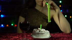 An attractive woman celebrates a holiday alone. Sad attractive woman celebrates the holiday, she sits at a table with a cake, a glass of wine and blowing a stock video footage