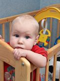 Sad baby. Standing in the cot Royalty Free Stock Image