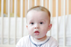Sad baby against white bed Stock Photo