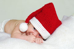 Sad baby age of 2 months in red New Year's hat. Lovely sad baby age of 2 months in a New Year's hat royalty free stock photo