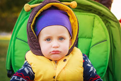 Sad baby boy sitting at the baby carriage Royalty Free Stock Images