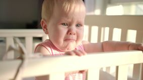 Sad baby crying in cot at home. Unhappy toddler standing in crib