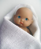 Sad baby doll. Sad blue eyed baby doll wrapped in white cloth on white background Royalty Free Stock Image