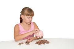 Sad baby girl looking at the piggy bank isolated. Sad baby girl looking at  the piggy bank  with coins on table isolated Royalty Free Stock Images