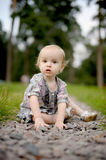 Sad baby girl sitting on the alley of stones Stock Photo
